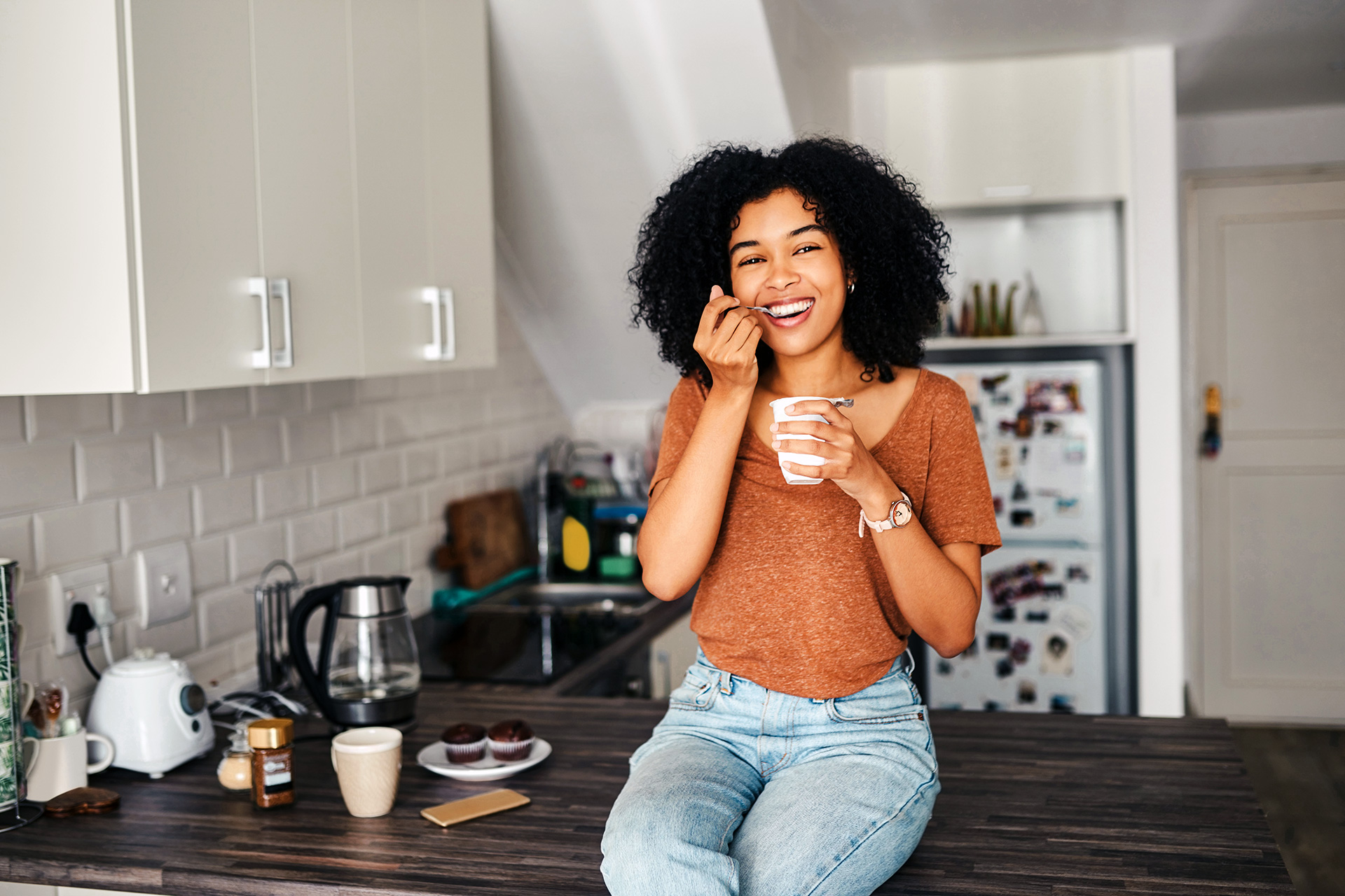 Young woman sitting on a counter eating