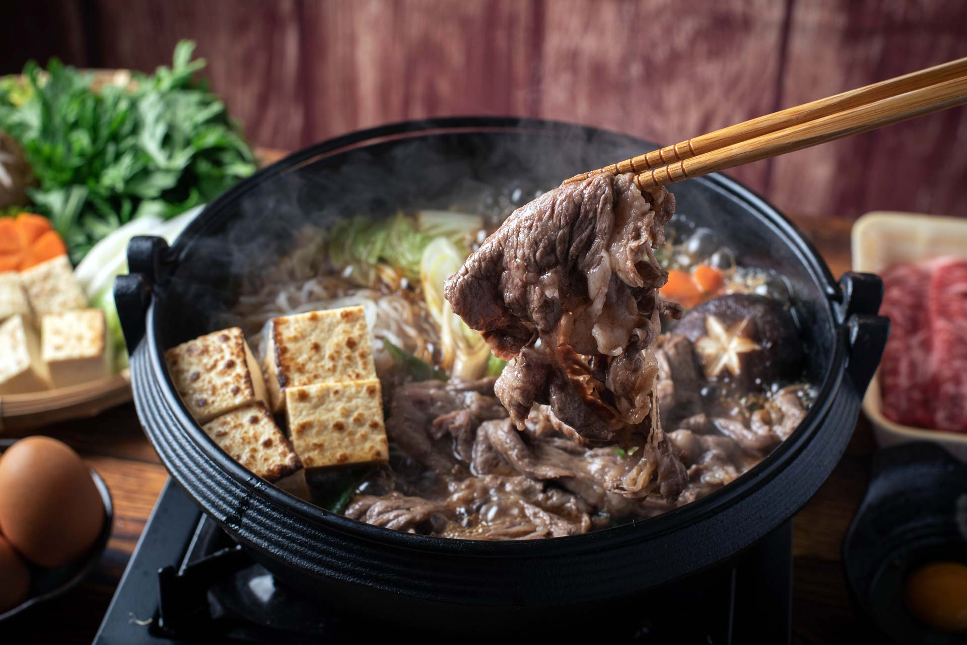 Chopsticks picking up cooked beef out of a bowl of soup